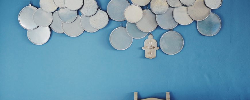 A pale blue wall with an interesting sculpture on the wall